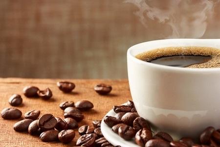 Kaffeetasse mit Kaffeebohnen auf Tisch