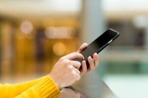In den Händen einer Frau ein schwarzes Smartphone als Testbericht für das nachhaltige Smartphones