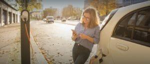 Elektromobilität ganzheitlich gedacht. Titelbild des Beitrags zeigt Frau an Pkw gelehnt vor Ladesäule mit Smartphone in der Hand.